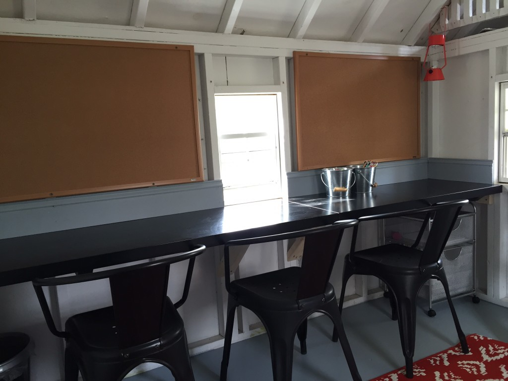 Black table top installed along the side wall of the clubhouse and paired with metal dining chairs.